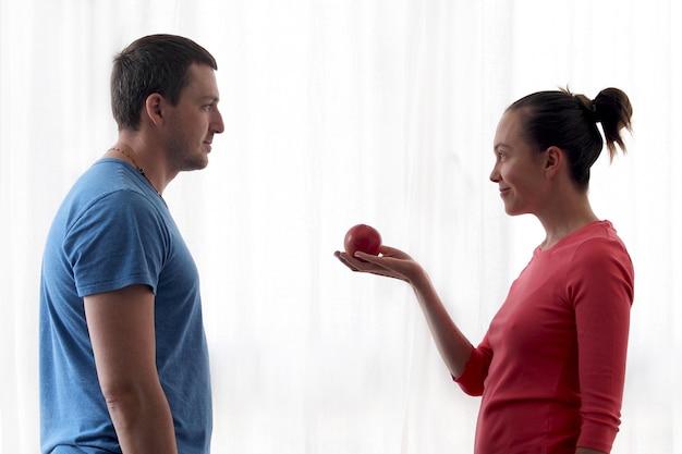 女性が男にリンゴを与える