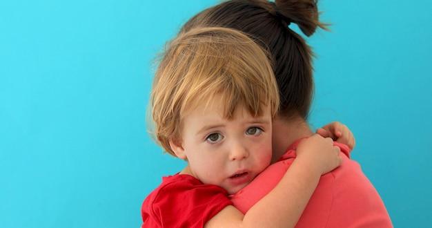 愛らしい小さな子供を抱き締める母