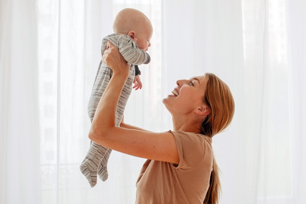 生まれたばかりの赤ちゃんと遊ぶこと幸せな家族の母