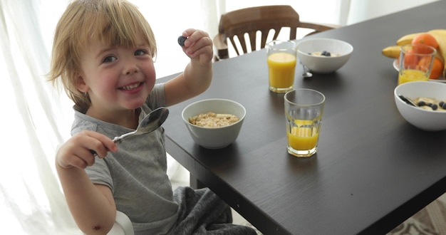 子供は朝食をとり、カメラを見て、部屋のテーブルで笑顔です。