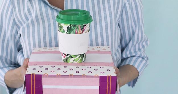 Женщина держит коробку пончиков и бумажный стаканчик кофе на синем