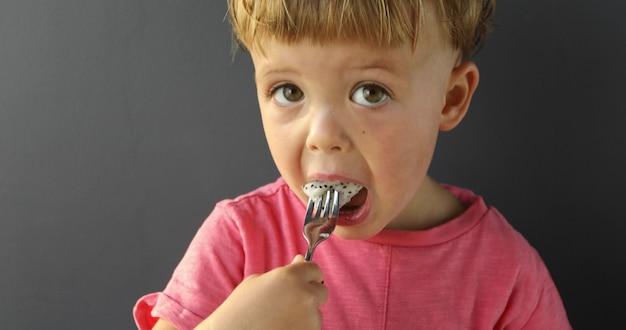 Безликий малыш в розовой футболке держит миску с нарезанной свежей сочной питайей