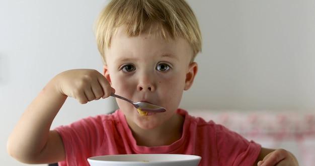 自宅のクローズアップで朝食にコーンフレークを食べる少年