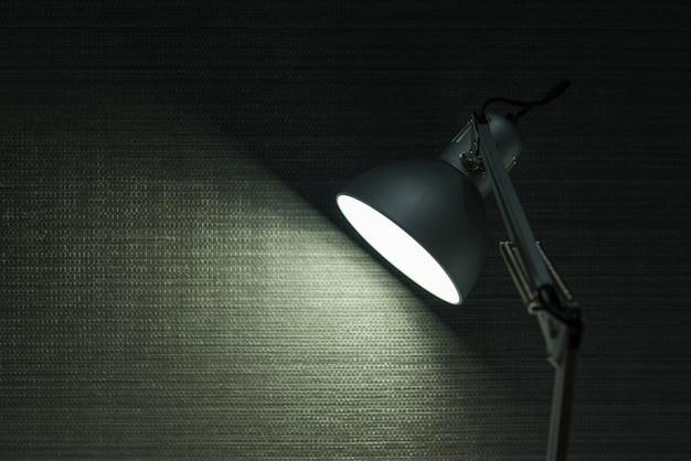 壁の背景に現代のデスクランプが点灯します。