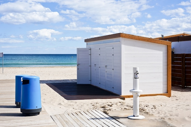 Деревянный дом на пляже, туалет, мусорные баки и вода
