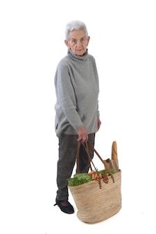 年配の女性が白で隔離される買い物に行く、