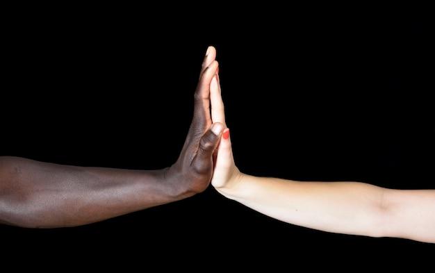 黒人男性と黒の背景に白人女性の手