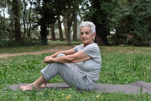 高齢者の女性が屋外でヨガを練習します。
