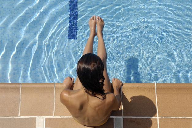 夏の日を楽しんでいるプール女性