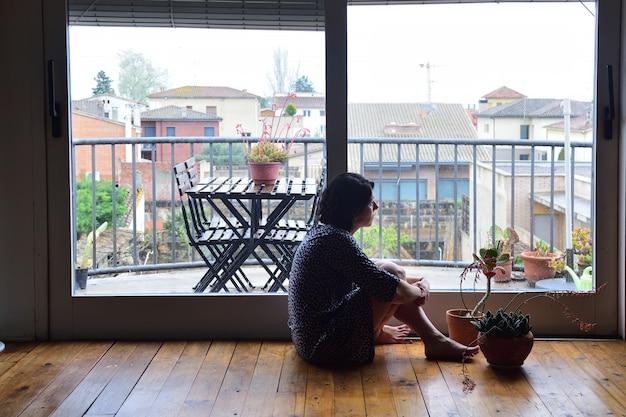 Грустная женщина сидит и смотрит в окно