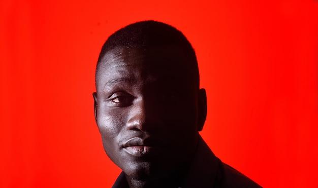 赤の背景に目を閉じてアフリカ人の肖像画