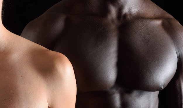 黒い背景に異人種間のカップルの抱擁