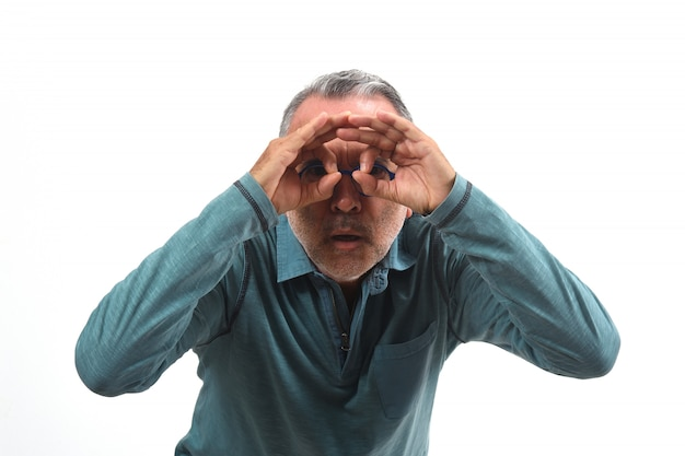 白い背景の上に眼鏡をかけているかのように指を通して見る男