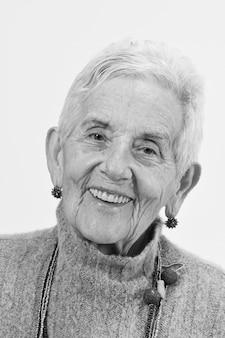 白い背景に笑みを浮かべて年配の女性の肖像画