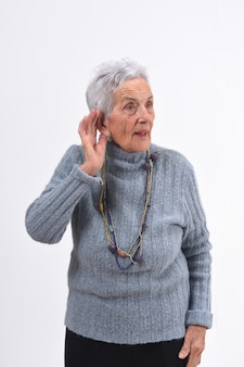 年配の女性は彼女が白い背景の上で聞くことができないので彼女の耳に手を置く