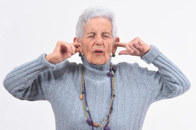 年配の女性が白い背景の上に彼女の耳を傷つけるノイズを作る