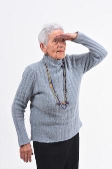 白い背景の上に離れている前に手を持つ年配の女性