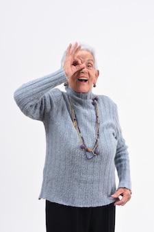 年配の女性が白い背景の上に眼鏡をかけているかのように指を通して見る