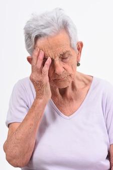 白い背景の上の頭痛を持つ年配の女性