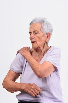 白い背景の上の肩の痛みを持つ年配の女性