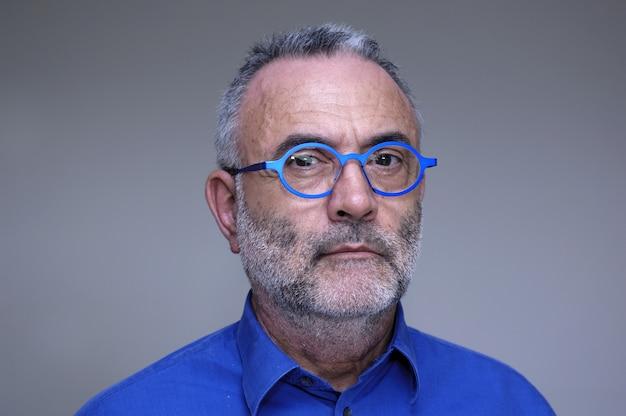 青いシャツとメガネの中年の男
