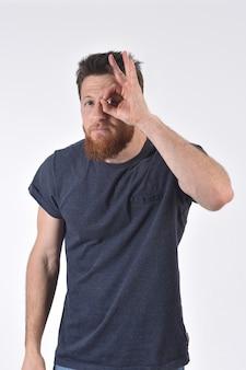 白の眼鏡をかけているかのように指を通して見る男