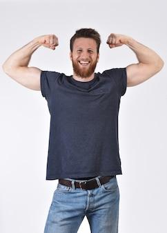 上腕二頭筋と勝利のサインを作る彼の腕を上げる男