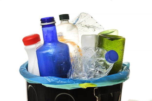 Мусорное ведро, полное бутылок для переработки на белом