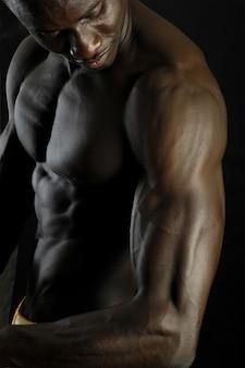 黒い背景のアフリカの男の子の上腕二頭筋