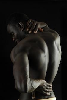 あなたは痛み、黒い背景があるので、背中に彼の手を持つ男