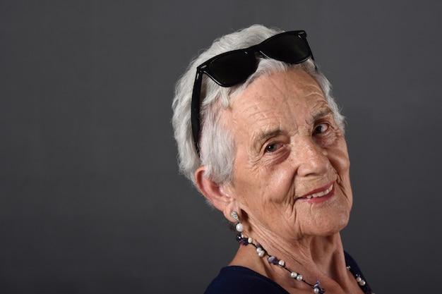 額に眼鏡をかけた年配の女性の肖像画