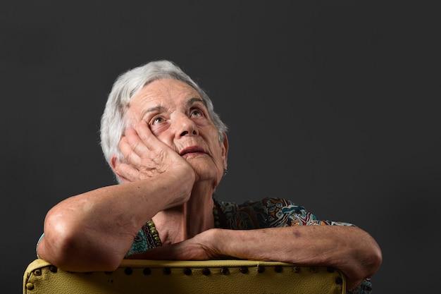 灰色の背景を持つ年配の女性の肖像画