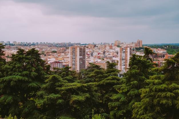 スペイン、マドリードの緑の木々と街の建物の空撮。