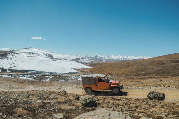雪に覆われた山脈、パキスタンに沿って曲がりくねった未舗装の道路の風景を見る。
