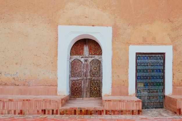 古いオレンジピンクの壁に木製のドアを刻まれた地元のアンティークモロッコパターン