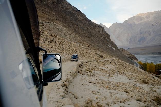 山道に沿ってオフロード車を運転する人々。