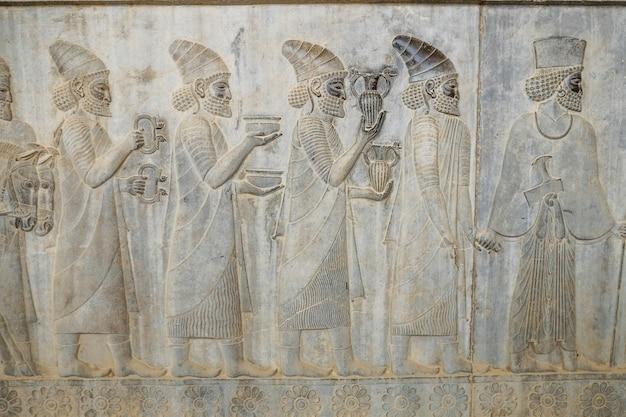 Барельефное изображение носителей дани несет подарок для короля в персеполе, иран.