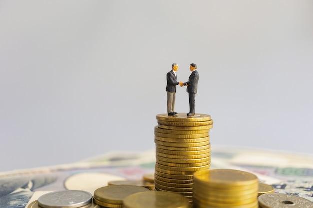 リーダーの実業家は、コインとお金のスタックの間で握手スタンドに適しています。