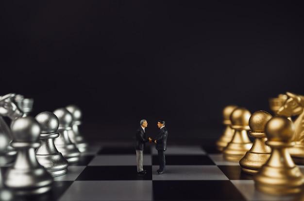 ミニチュアビジネスパートナーシップハンドシェイクコンセプト。金と銀のチェスの取引後の成功したビジネスマンハンドシェイク