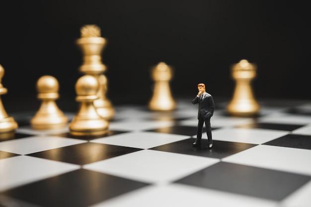 ストラテジストのビジネスマンのミニチュアは、問題の概念を修正