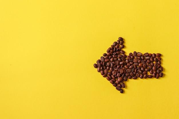 黄色の背景に分離された矢印の形をしたコーヒー豆。