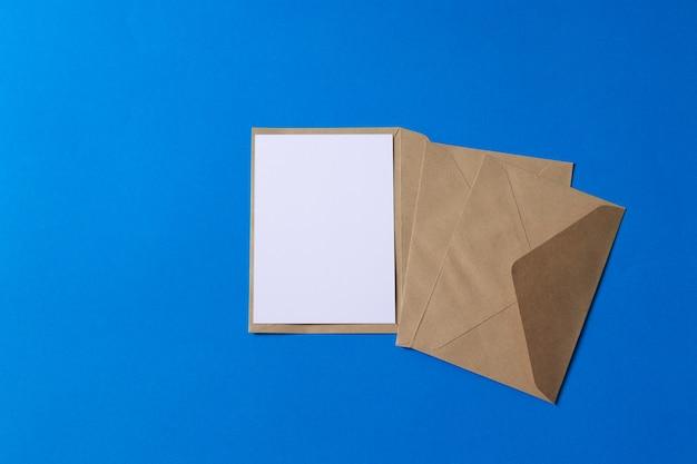 Макет коричневого крафт-конверта с пустой белой карточкой