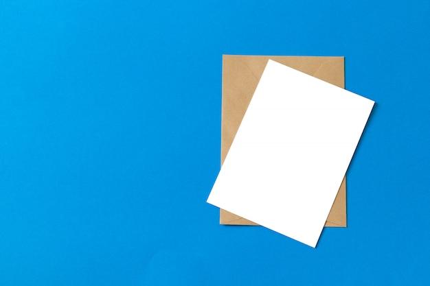 青い背景に分離された空白の白いカードを持つモックアップ茶色クラフト封筒文書