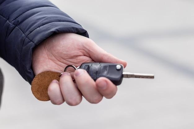 Ключ от машины в руке человека на фоне автомобиля
