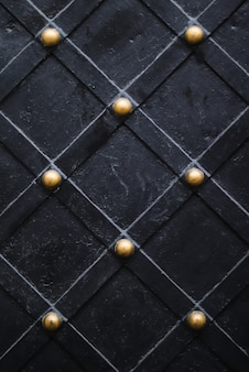 Черная дверь со старыми золотыми металлическими элементами текстуры