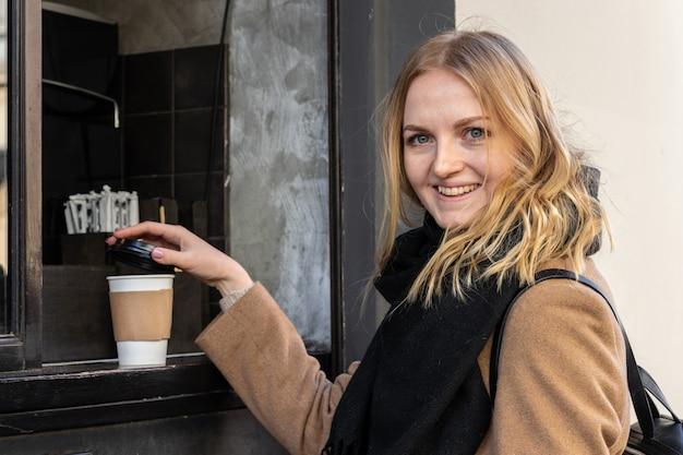 コーヒーはカフェショップで持ち帰ります。ホットコーヒーの紙コップを取って女性の手を閉じる