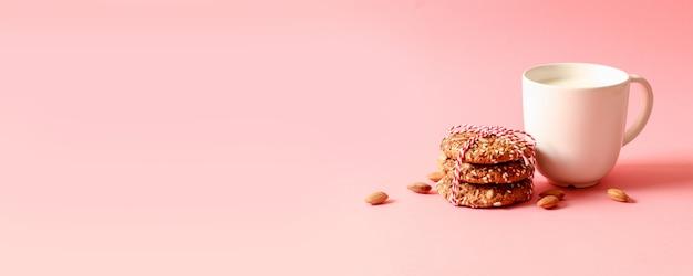 オートミールチップクッキー、ナット、ピンクの背景にミルクのカップ。コピースペース