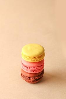 ベージュ色の背景にカラフルな甘いマカロンクッキーの盛り合わせ