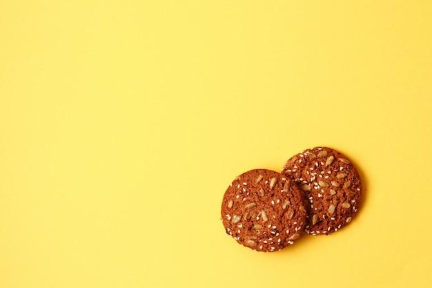 コピースペース、上面と黄色の背景ボード上の新鮮なオートミールクッキー。