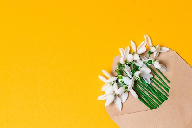 春のフラワーアレンジメントとクラフト封筒。オーバーヘッドビュー。フラットレイアウト、平面図の招待状。